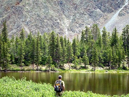 Angler approaching a beautiful high mountain lake