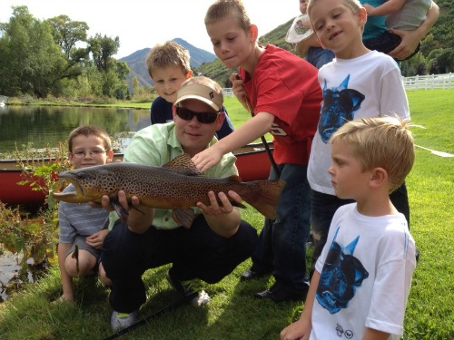 Slilde: Photo of angler holding large trout, surrounded by young boys
