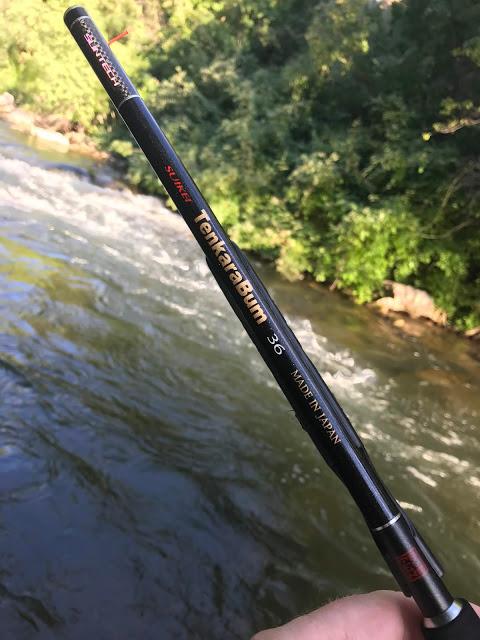 Angler holding TenkaraBum 36 rod, with stream in background