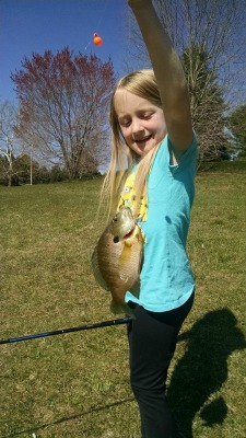 Young girl showing off the sunfish she caught.