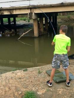 Child fighting a carp with a Nissin Kyogi