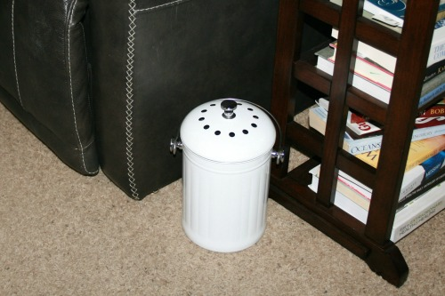White pail in a living room by chair and small bookshelf.