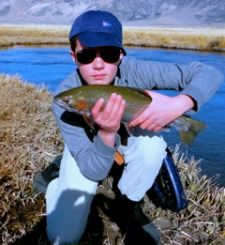 Young angler holding large rainbow trout