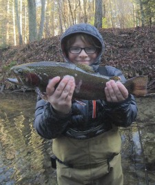 Child with big smile holding big trout