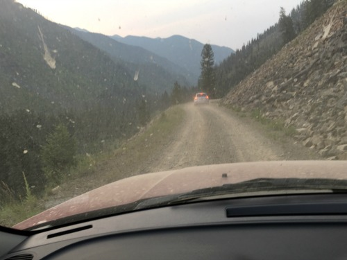 View through the windshield of a narrow, dirt road. No shoulder and steep drop.