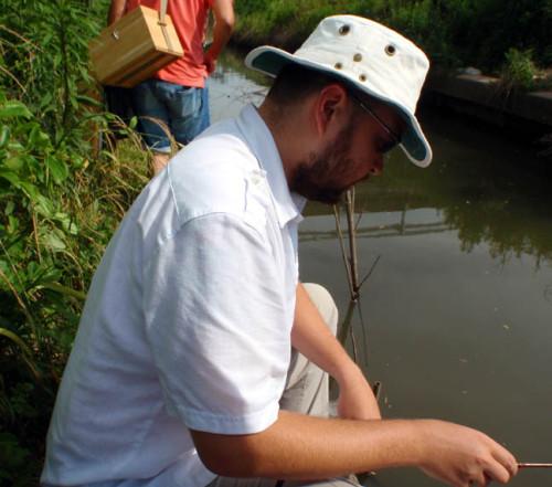 Angler sitting at water's edge.