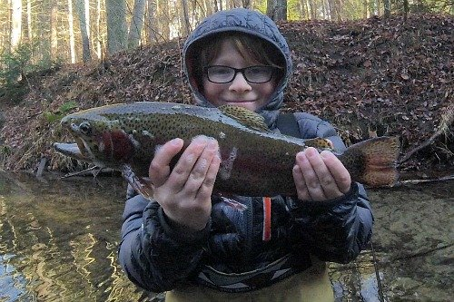 Smiling angler holding large rainbow trout
