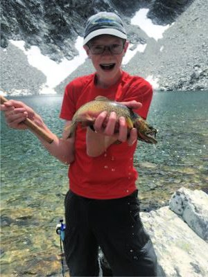 Young angler showing off cutthroat trout